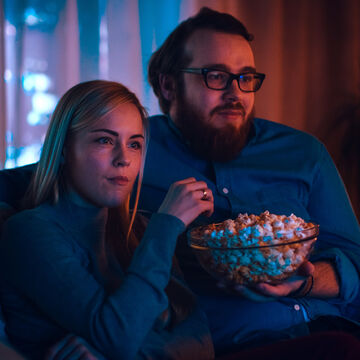 Couple in home theatre eating popcorn